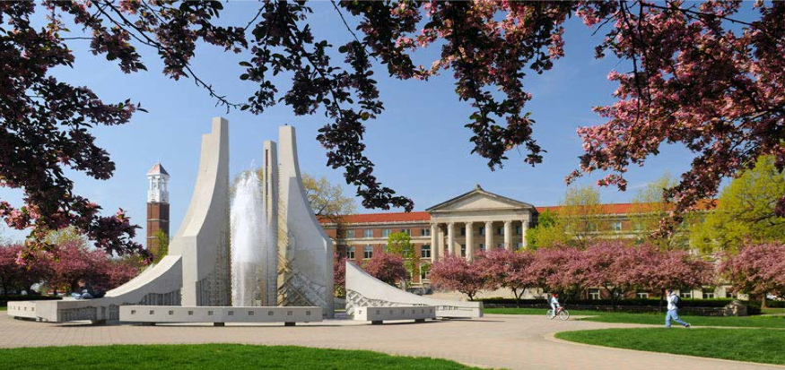 The Engineering Fountain, also known as the Purdue Mall Water Sculpture, with the Purdue Bell Tower in the background. The fountain serves as free shower for students to cool off during scorching Midwest summer. Source: Purdue University.