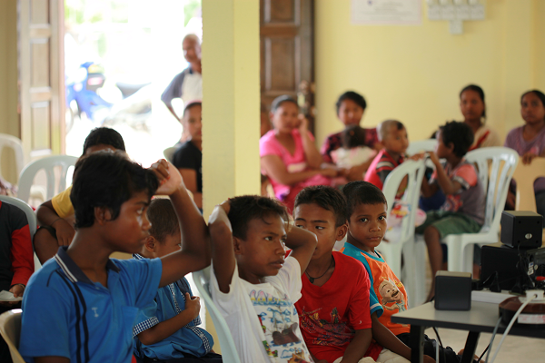 The Orang Asli children watching a movie as they wait patiently in the hall for their sample to be taken by Dr. Ang and his team.